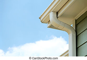 Rain gutters on a home. There is a blue sky with a fluffy white cloud in the background.