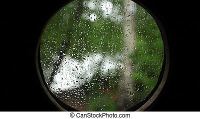 Rain in the round porthole looking - Rain through the...