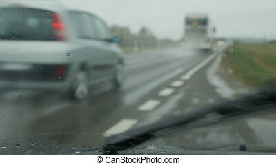 Rain is pouring on car glass.