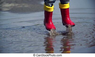 Rain Joy - Close up of unrecognizable kid feet in rubber...