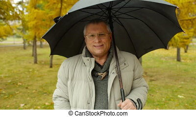 Rain Man - Close up of senior man holding umbrella and...