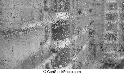 Rain on a window, buildings in background. Black and white....