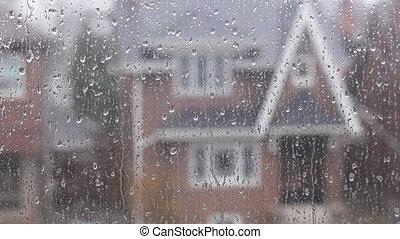 Rain on suburban window. House.
