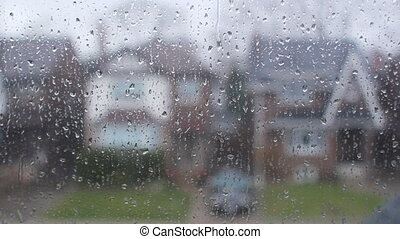 Rain on suburban window. Houses.