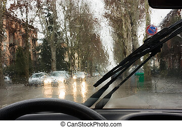 rain on the road - looking road through the car windshield ...