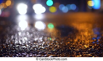 Rain road traffic night - Low shot of puddle whilst it rains...