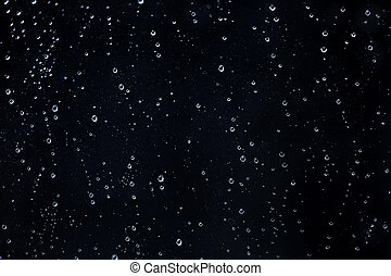 Rain water drops on a black dramatic window glass. Autumn depression background. Rain pattern
