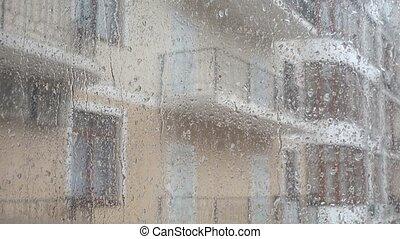 Rain, water drops on a window, buildings in background. -...