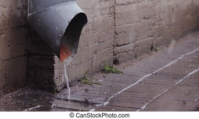 Rain water flowing from drain pipe closeup. HD