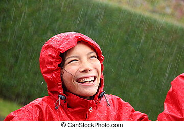 Rain woman - Young woman wearing a red raincoat enjoying the...