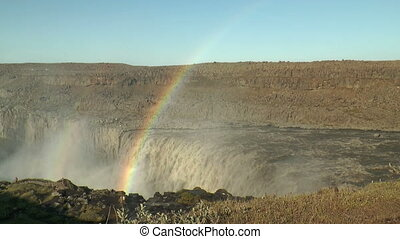 rainbow above detifoss waterfall in iceland visited by...