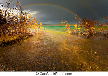 Rainbow and dark clouds over large lake - A Thundershower...