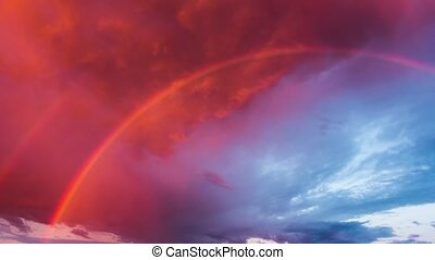 Rainbow and storm clouds at sunset, time-lapse