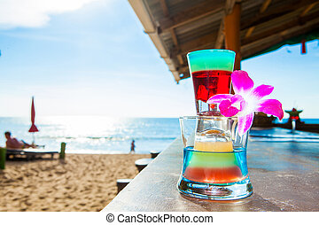 rainbow cocktail tower on beach, blue sea and sky background
