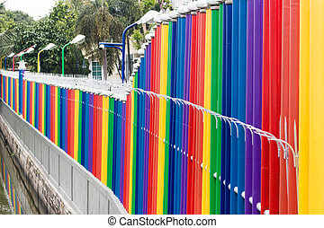 Rainbow color fence with concrete wall