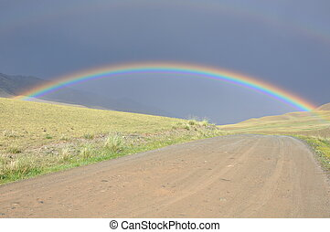 Complete rainbow crossing a road in the Tian Shan mountains