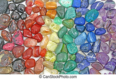 Background of red, orange, yellow, green, blue and purple colored tumbled crystal stone depicting the seven chakras