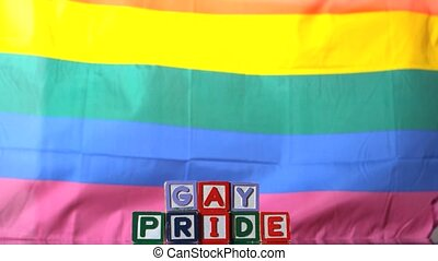 Rainbow flag blowing in the breeze with gay pride blocks in...