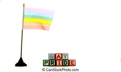 Rainbow flag blowing in the wind beside gay pride blocks in...