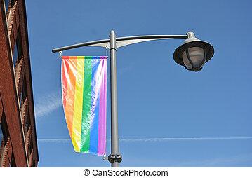 Rainbow flag on the sky background