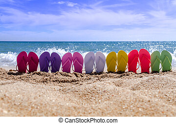 Line of brightly colored flip flops arranged in a rainbow on beach with waves breaking on beach