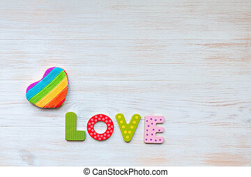 Rainbow heart pillow and word LOVE in wood letters on wooden vintage board. Mockup for LGBT. Valentines day concept.