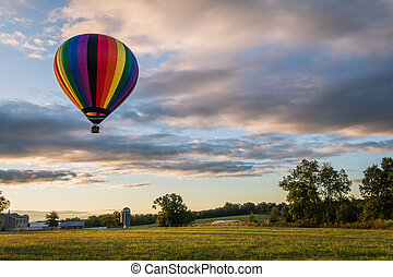 Rainbow hot-air balloon in blue sky over field at sunrise