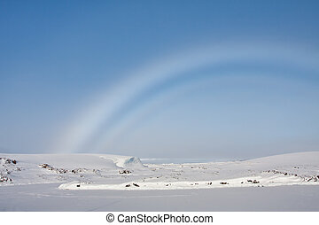 rainbow in Antarctica - rainbow over snow-covered slopes of...
