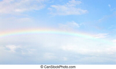rainbow in blue sky with clouds