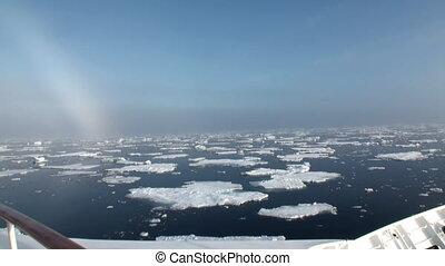 Rainbow in ocean among icebergs and ice in Arctic. - Rainbow...