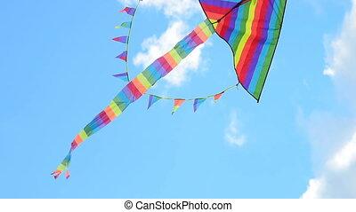 Rainbow kite flying against blue sky