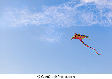 Rainbow kite flying in the blue sky