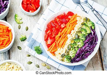 rainbow millet vegetable salad on white wood background....