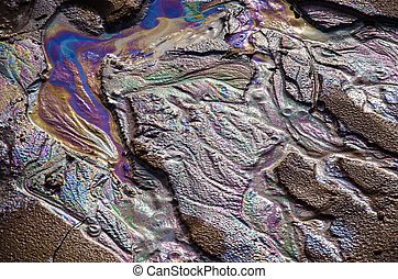 Rainbow oil slick on the sand. Textured background. Pollution of water and ground concept.