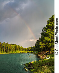 Rainbow over a lake surrounded by forest.