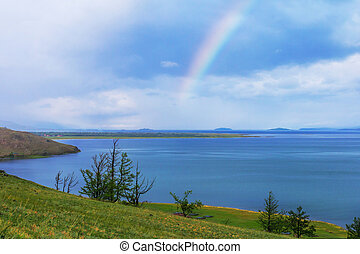 Rainbow over calm water of taiga lake