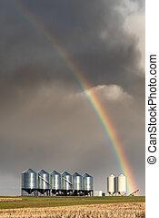 Rainbow over grain bins during spring storm on the prairies in Saskatchewan