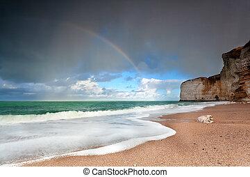 rainbow over ocean coast by cliff