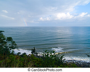 Rainbow Over the Ocean with a Partly Cloudy Sky