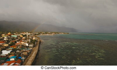 Rainbow over the sea and the coastal town. Catanduanes island Philippines.