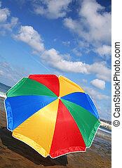 Rainbow Parasol - Rainbow parasol on the beach with dramatic...