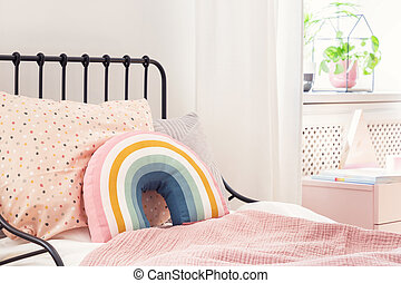 Rainbow pillow and pink sheets on girl's bed in bright bedroom interior with plant. Real photo