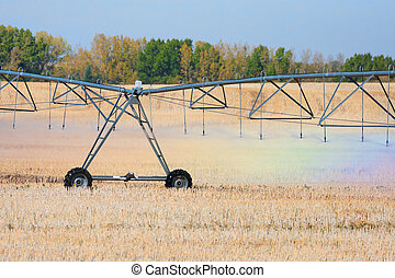 A rainbow of colors are reflected in the water droplets coming from an agricultural watering system pivot.