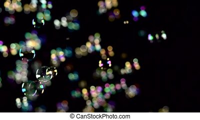 Rainbow soap bubbles fly. Slow motion. Black abstract...