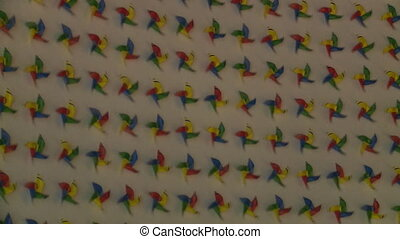 Rainbow spin pinwheels spin on white wall background -...