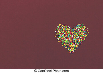 Rainbow sprinkles heart on red background. Toned.