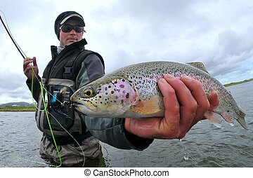 Wide angle view of a fly fisherman holding a wild rainbow trout caught in Alaska