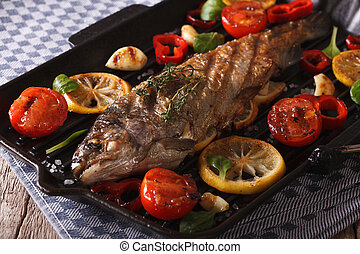 rainbow trout with vegetables on a grill pan close-up. horizontal