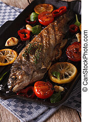 rainbow trout with vegetables on a grill pan close-up. Vertical