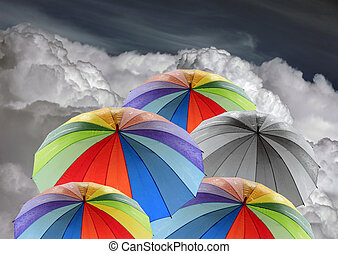 Rainbow umbrellas against blue sky
